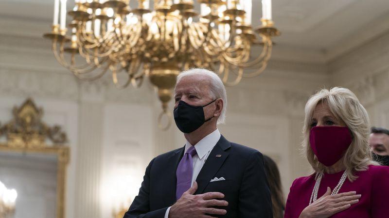 President Joe Biden, accompanied by first lady Jill Biden, places his hand over his heart...