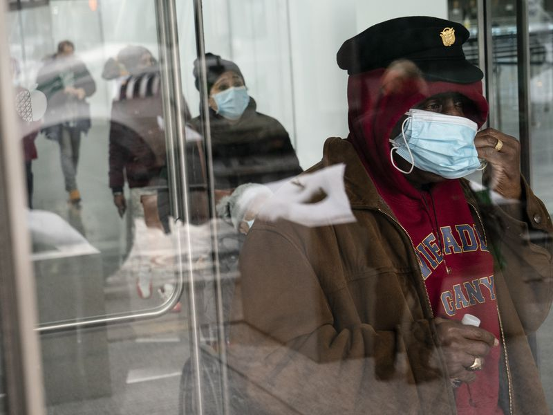 FILE - In this Feb. 3, 2021 file photo, a patient adjusts his face mask as he leaves a COVID-19...