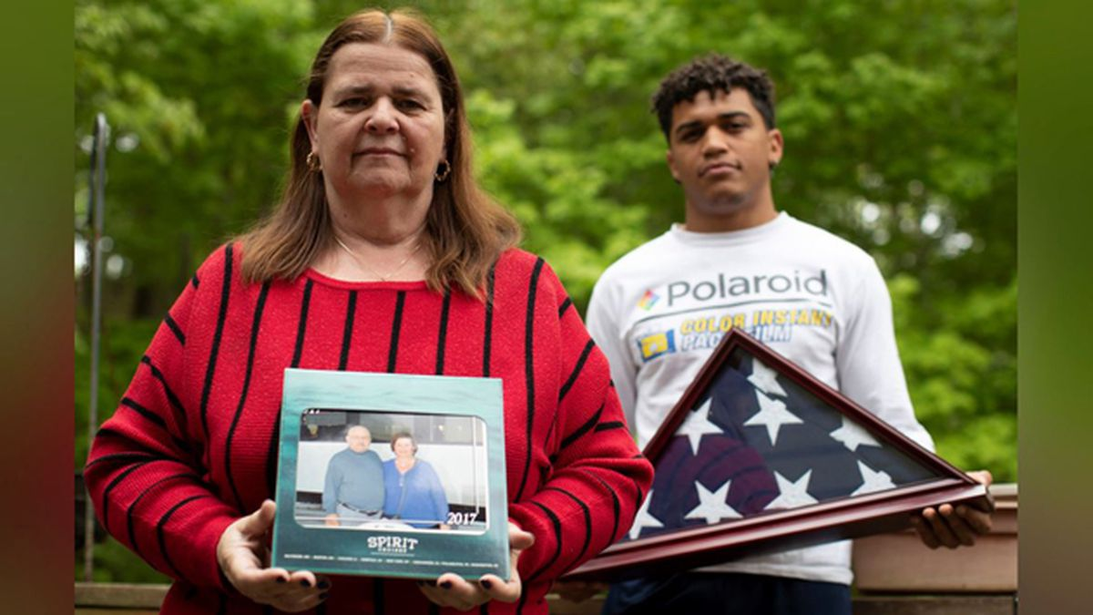 In this Friday, May 22, 2020 photo, Florence Hopp, left, holds a photograph of herself and her husband Robert Hopp during a cruise in 2017, as her son J.J. Brania-Hopp holds the American flag the military presented to them after his father's death at their home in Boonton, N.J. Hopp was one of at least 79 residents of a veterans home in Paramus, New Jersey, to die from COVID-19, making the state-run facility one of the nation's worst hot spots for the virus. (AP Photo/Mary Altaffer)