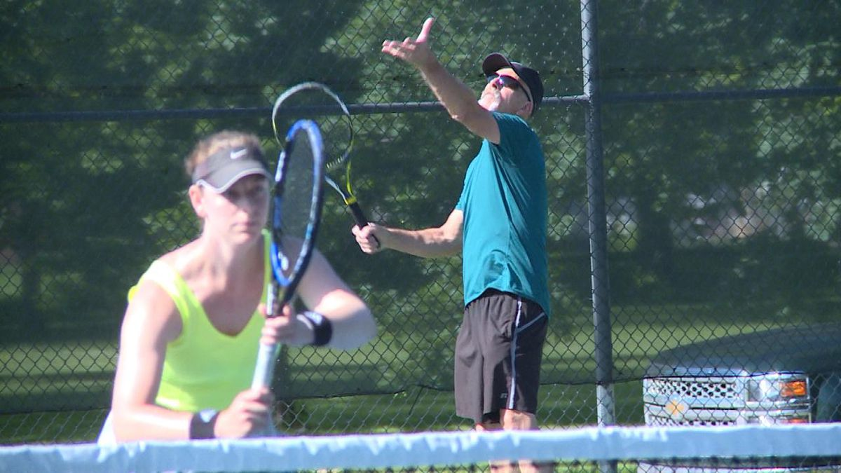 Bryan Dorr prepares to serve in the mixed-doubles tennis tournament at Cody Park (Credit: Patrick Johnstone/KNOP-TV)