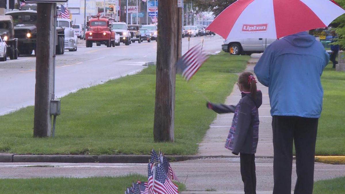 Families stand outside their homes to watch the parade and wave their flags. The flyover is rescheduled for Tuesday at 10:15 am. (SOURCE: Kaylie Crowe KNOP-TV)