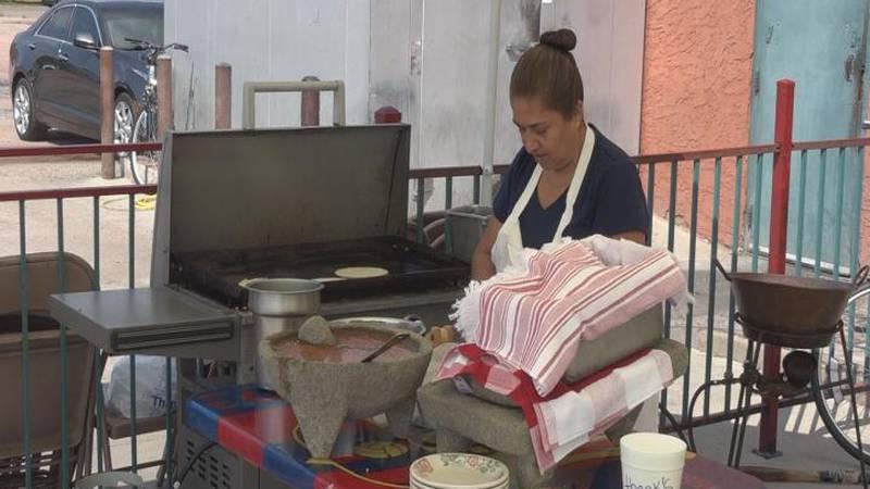 Three Margarita's cook outside demonstrating how to make homemade corn tortillas.