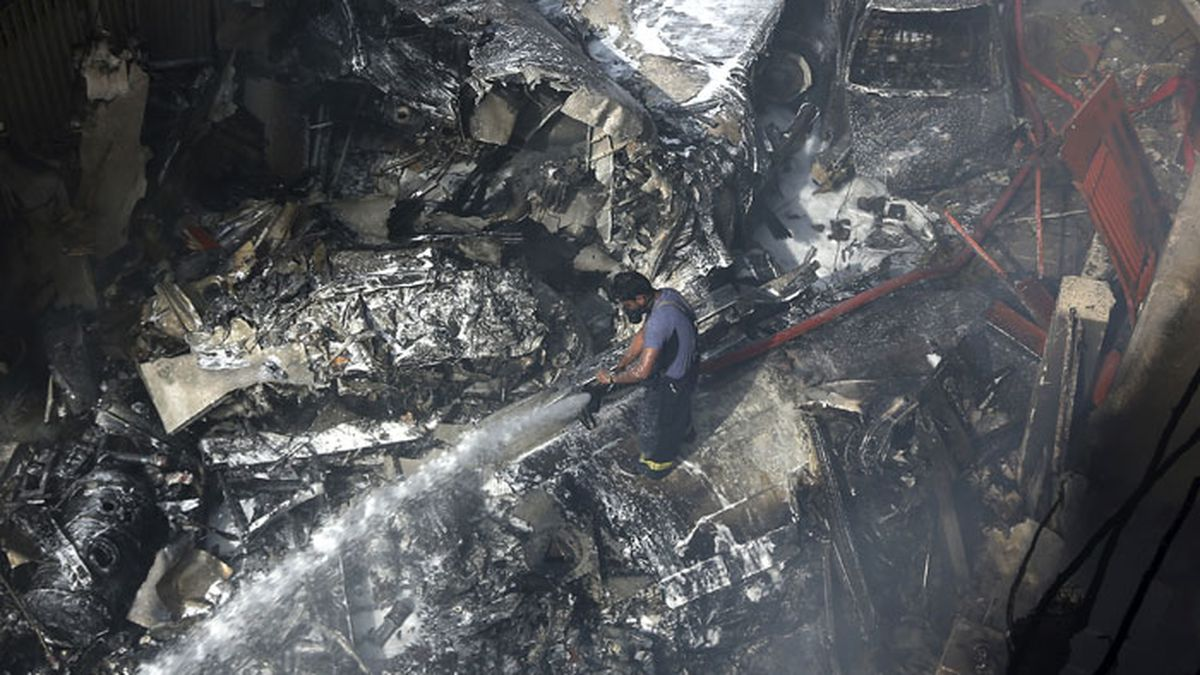 A firefighter tries to put out fire caused by plane crash in Karachi, Pakistan, Friday, May 22,...