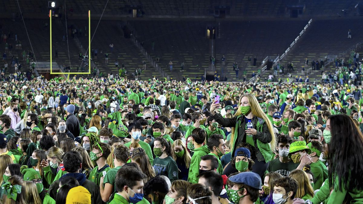 Fans storm the field after Notre Dame defeated the Clemson 47-40 in two overtimes in an NCAA...