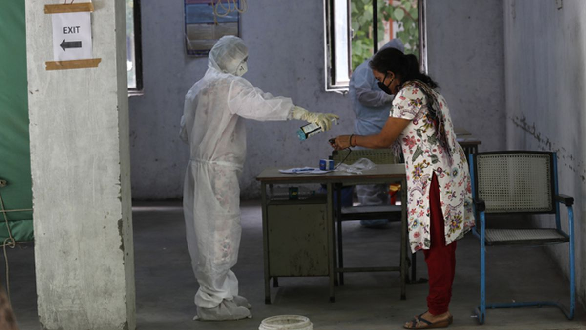 A health worker gives hand sanitizer to a woman after taking her sample for the COVID-19 rapid antigen test in New Delhi, India, on Friday, June 19, 2020. (AP Photo/Manish Swarup)