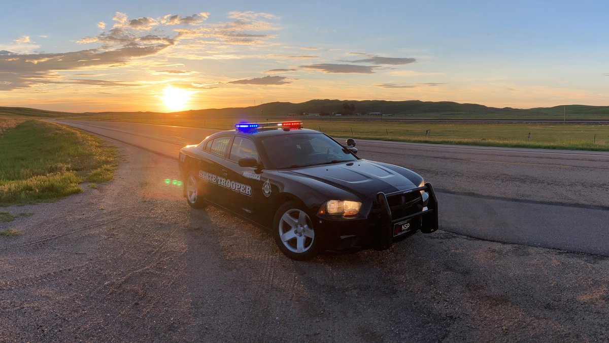 A Nebraska State Patrol cruiser parked on the side of the road with sun setting in background.