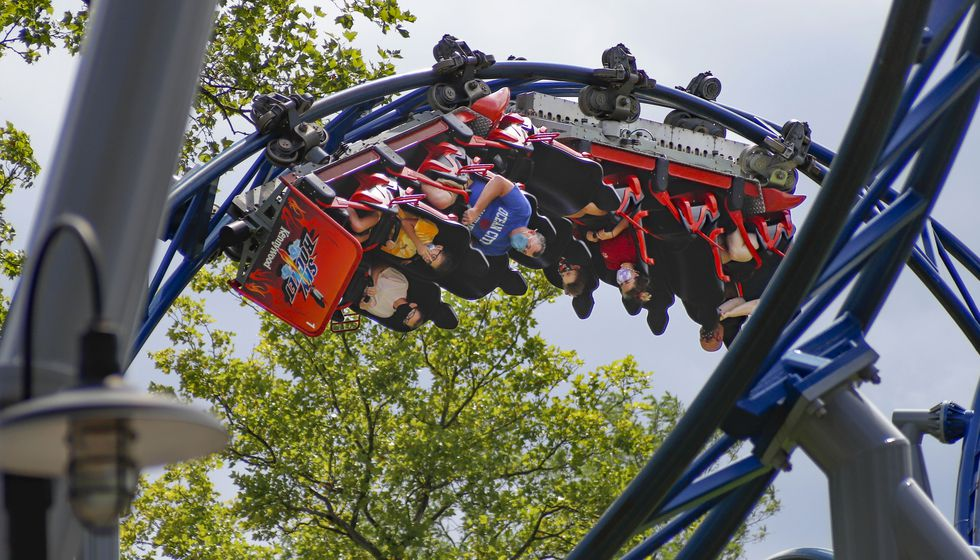 "In this photo made on Saturday, Aug. 29, 2020, riders of the ""Phantom's Revenge"" roller coaster are inverted as they go through a loop during the ride at Kennywood Park in West Mifflin, Pa. Visitors have been slow to return to U.S. theme parks that saw their seasons interrupted by the coronavirus crisis, causing some parks to reduce their operating days, slash ticket prices and close early for the year."