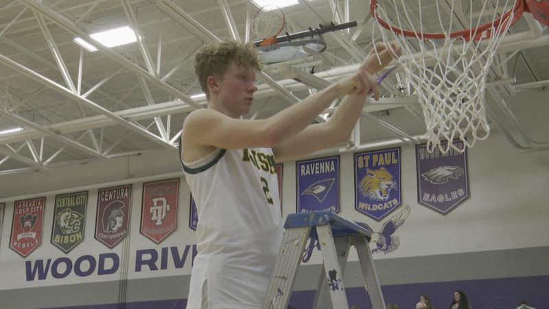 Jack Heiss cuts the net after an impressive victory to qualify for the State Tournament.