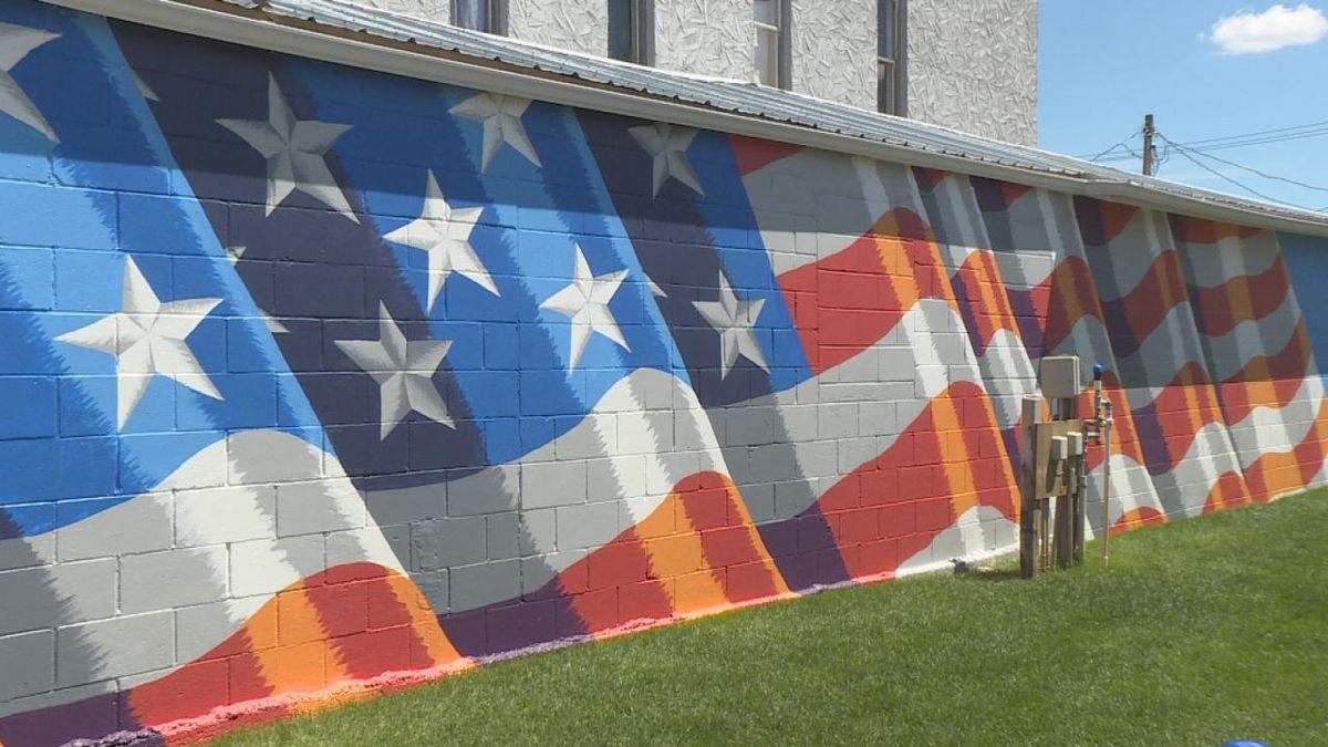 Lumberyard owner, Heidi Beaumont, had the idea to redo an aging mural behind the Veterans Wall in Ansley Nebraska. The week long process took many hours of power washing, priming, redrawing, and painting. (SOURCE: Kaylie Crowe KNOP-TV)