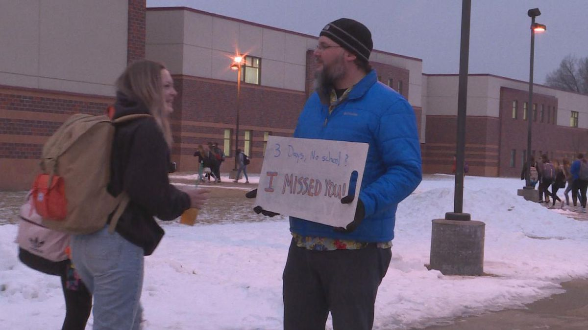 Teacher stands outside school with sign to encourage students. (SOURCE: Kaylie Crowe KNOP-TV)-