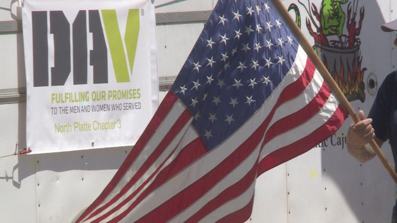 Members of DAV stand outside of the Cajun Prairie trailer holding an American flag.