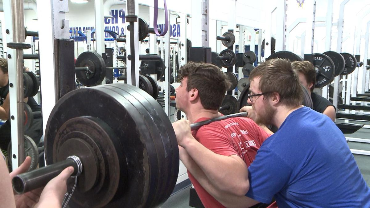 Matthew Musselman, spotted by Austin Junker, and other North Platte lifters, squats 475 lbs. (Credit: Patrick Johnstone/KNOP-TV)