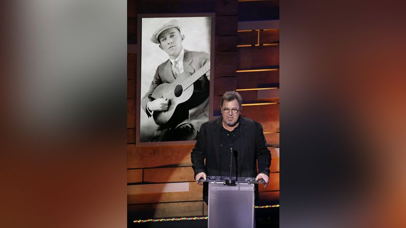 Vince Gill speaks under a picture of Jimmie Rodgers, known as the Father of Country Music,...